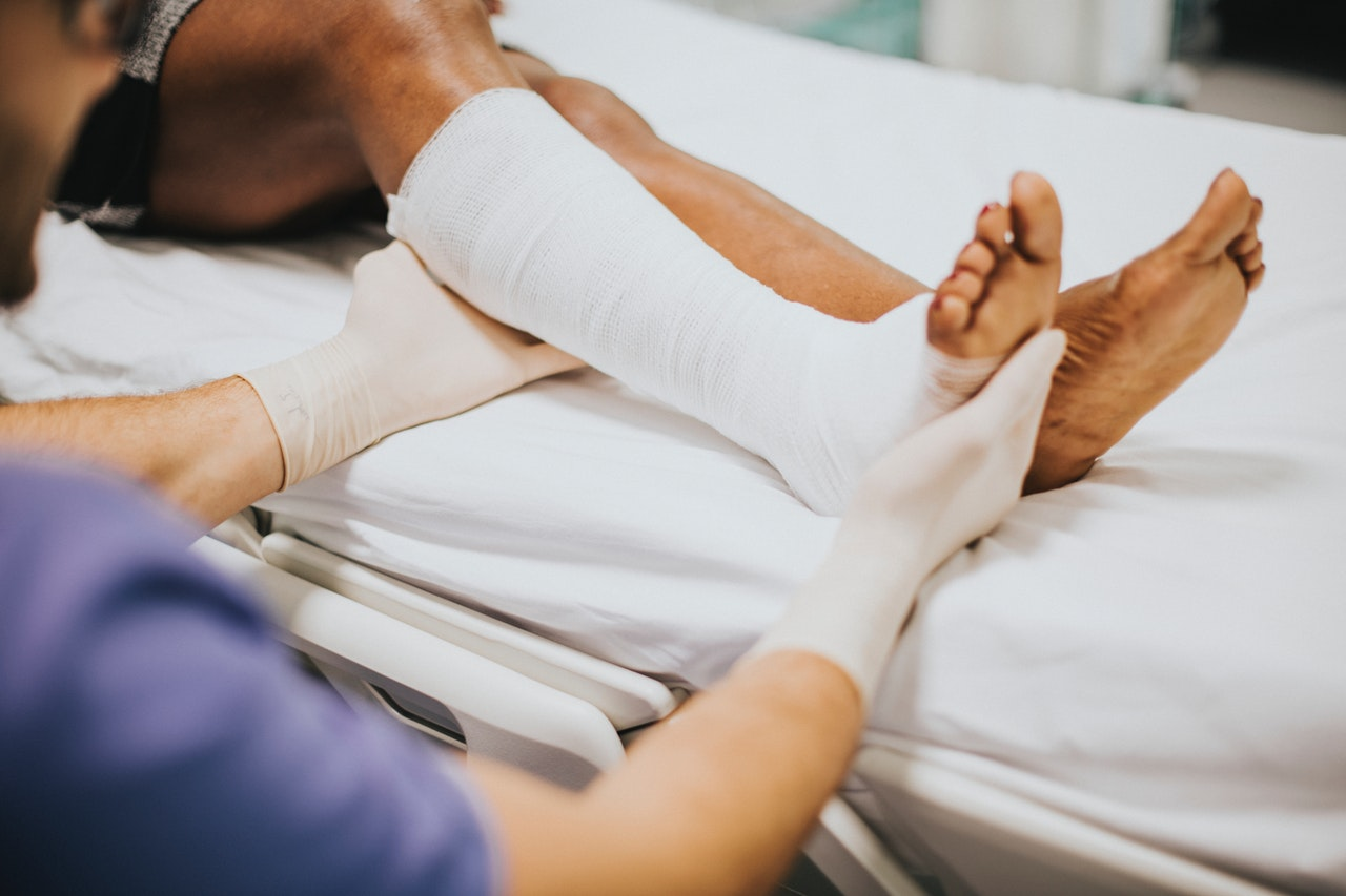 Doctor wearing surgical gloves treating patient with broken leg